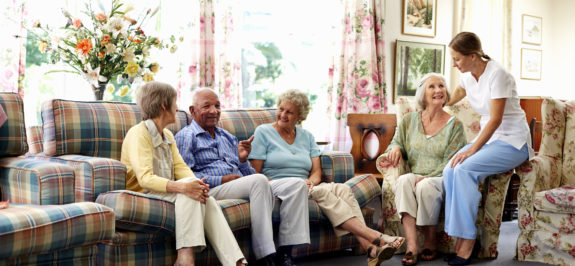Female caretaker spending leisure time with senior people in nursing home